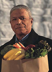 Photo: Older man carrying a bag of fruits and vegetables.