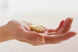 Photo: A hand holding pills.