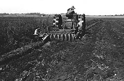 Photo: A tractor equipped with steel wheels pulling a 1937 disk plow through a field.