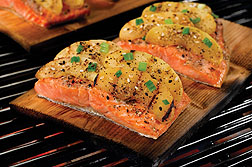 Cooked salmon fillets with apple slices on a grill.
