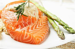 Photo: A fillet of salmon on a plate with two asparagus spears.