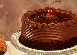 Photo: A chocolate cake on a glass cake stand. Link to photo information.