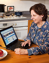 A woman using a laptop to access the nutrient database. Link to photo information